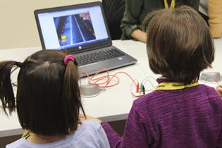 Un niño y una niña frente a un ordenador portátil