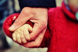 Un adulto sujetando la mano de un niño
