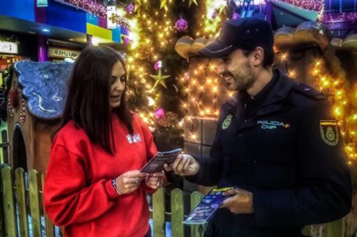 Un agente de la Policía Nacional dándole un folleto a una chica sobre Comercio Seguro